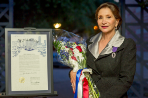 """Josée Larsen holding flowers, wearing the Chevalier dans l'Ordre de Palmes Académiques award on her lapel, standing beside a Mayoral Proclamation declaring """"Josee Larsen Day"""" in Houston."""