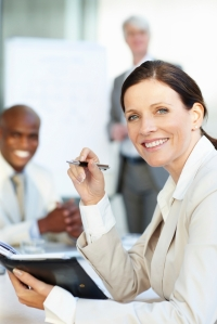 Portrait of smiling business woman noting something with team in background