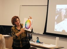 Artist and instructor Ellen Orseck demonstrates the color wheel during a preview of her upcoming art classes.