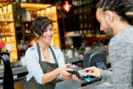 Man paying by credit or debit card at a restaurant to a happy waitress - food and drinks concepts